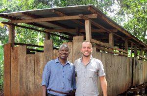 """Der Geislinger Tim Zajontz zusammen mit Roy Mwesigwa vor einem Schweinestall der Frauengruppe """"Faith and Love"""" im ugandischen Jinja."""